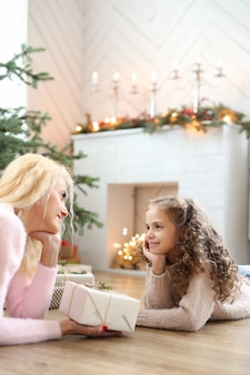 Mutter und tochter im weihnachtlich dekorierten wohnzimmer