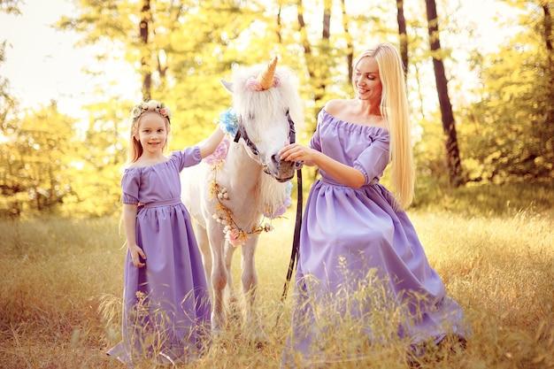 Mutter und tochter in ähnlichen lavendelkleidern streicheln ein einhornpferd. sommerwiese