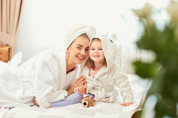 Mutter und tochter in bademänteln und handtüchern auf dem bett im ro