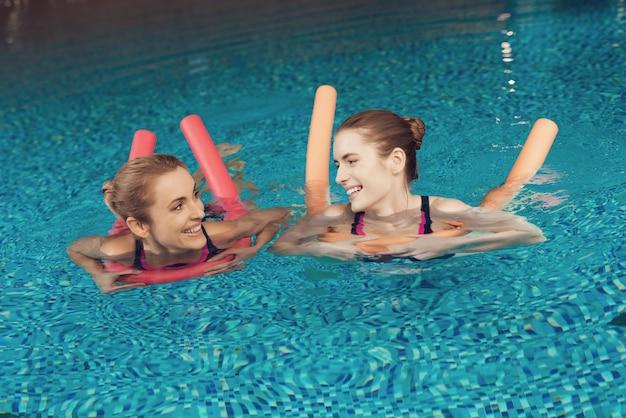 Mutter und tochter in den badeanzügen schwimmend im pool an der turnhalle.