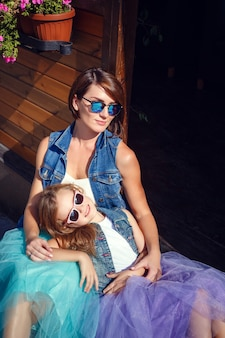 Mutter und tochter in den sommerferien spazieren entlang der promenade am meer in einem café.