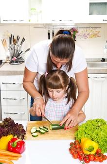 Mutter und tochter in der küche, die gemüse zubereitet