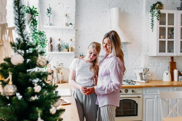 Mutter und tochter in der küche zu weihnachten dekoriert, tee oder kakao trinken, sich unterhalten, auf gäste warten
