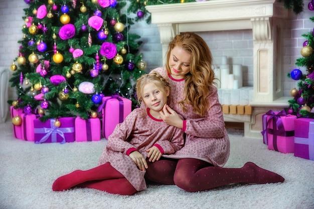 Mutter und tochter in der nähe des weihnachtsbaumes im fotostudio
