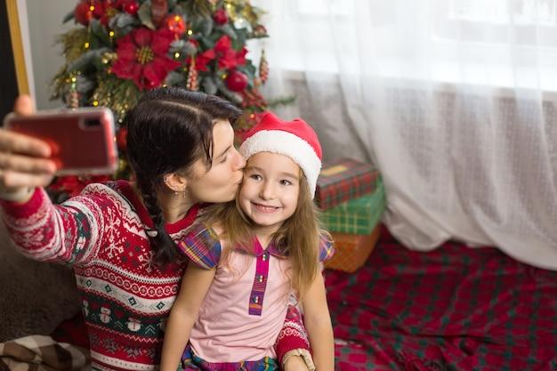 Mutter und tochter in der nähe des weihnachtsbaumes machen fotos und selfies am telefon