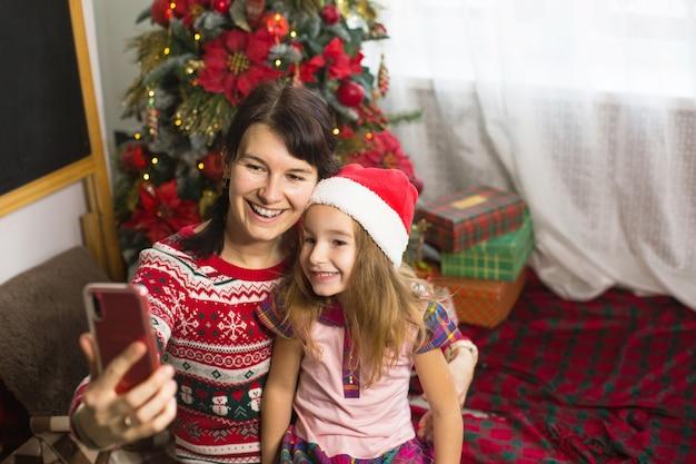 Mutter und tochter in der nähe des weihnachtsbaums machen fotos und selfies am telefon und kommunizieren per video