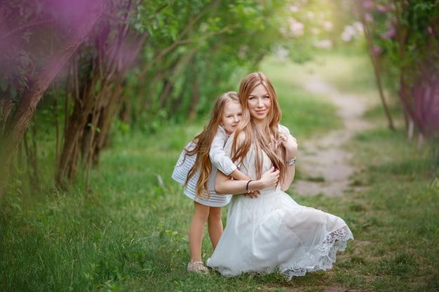 Mutter und tochter in der nähe eines blühenden busch-, frühlings-, frühlingsfamilienfoto-shootings
