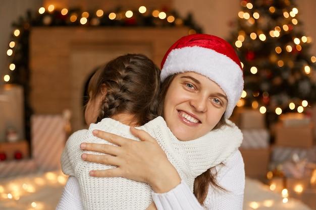 Mutter und tochter in der nähe von weihnachtsbaum und kamin umarmen sich mit glück