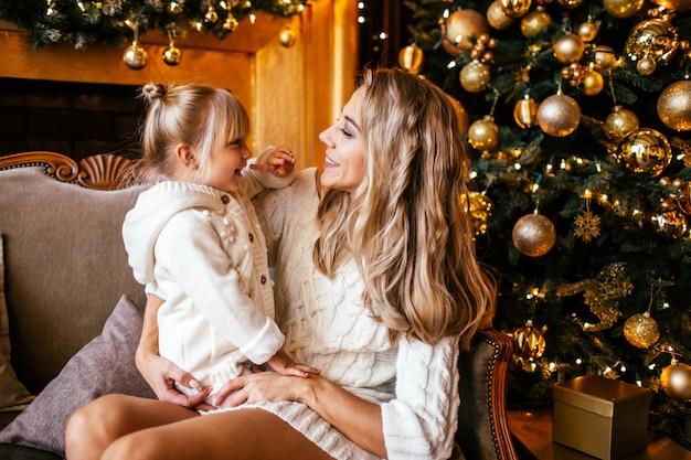 Mutter und tochter in der weißen strickenden kleidung umarmend und lächelnd, winter in einem verzierten wohnzimmer am weihnachtsabend zusammen glättend. familienglück
