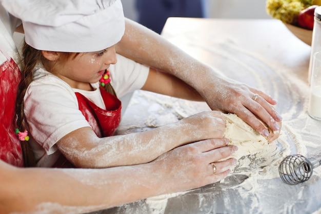 Mutter und tochter in derselben kleidung haben spaß daran, einen teig in einer gemütlichen küche zuzubereiten