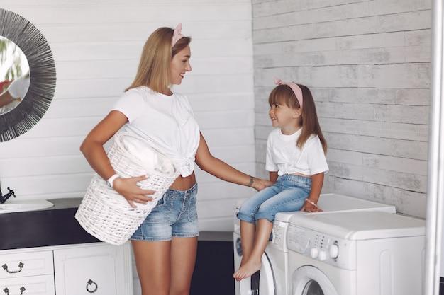 Mutter und tochter in einem badezimmer in der nähe von waschmaschine