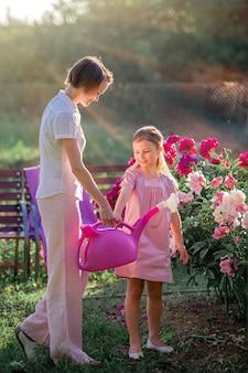Mutter und tochter in einem leinenrosa kleid kümmern sich um pfingstrosen im garten, gießen die blumen. er lächelt perfekt und lacht. beleuchtet von den strahlen der untergehenden sonne am abend.
