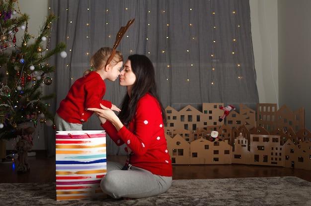 Mutter und tochter in einem roten pullover zu weihnachten am weihnachtsbaum. bleib zu hause für die feiertage.
