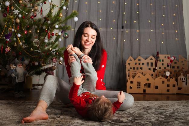 Mutter und tochter in einem roten pullover zu weihnachten am weihnachtsbaum. ein mädchen und ihre mutter umarmen sich und küssen sich zu hause am weihnachtsbaum