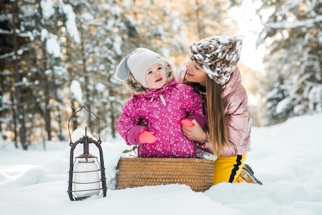 Mutter und tochter in einen schal in einem verschneiten winterwald gewickelt. reisen und erholung