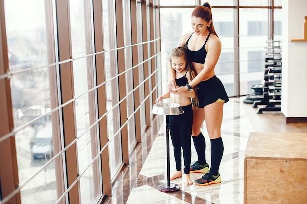 Mutter und tochter in einer turnhalle trainieren