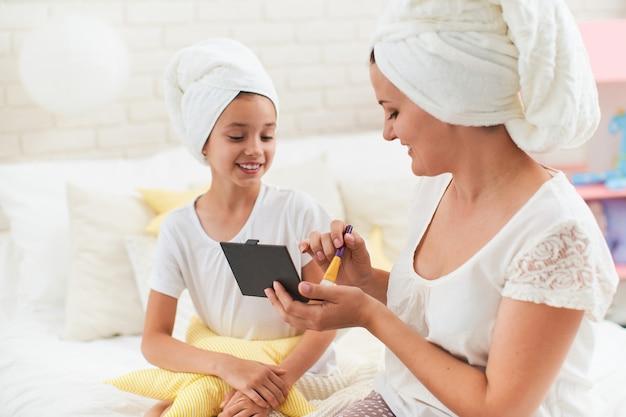 Mutter und tochter in handtüchern auf dem kopf, make-up selektiver fokus zur hand