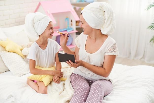 Mutter und tochter in handtüchern auf dem kopf, schminken sich und haben spaß