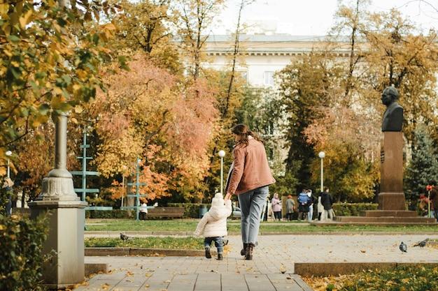 Mutter und tochter in herbstkleidung und schuhen spazieren durch den park. kleine tochter mit ihrer mutter spazieren im herbst durch die stadt