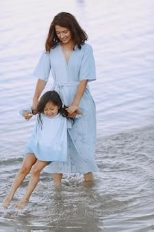 Mutter und tochter in identischen kleidern. familie spielt am fluss.