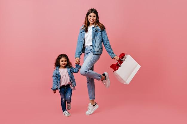 Mutter und tochter in jeans händchen haltend. studioaufnahme der glücklichen familie, die auf rosa hintergrund aufwirft.