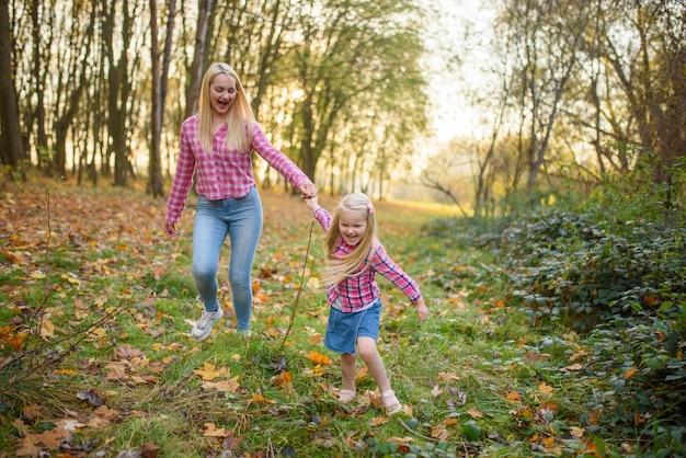 Mutter und tochter in jeans und rosa hemden gehen im herbstpark spazieren.