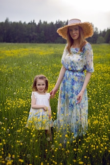 Mutter und tochter in kleidern und hut stehen am sommertag auf einem gelben blumenfeld