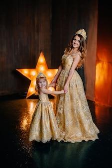 Mutter und tochter in luxuriösen kleidern auf dem hintergrund der neujahrsdekorationen