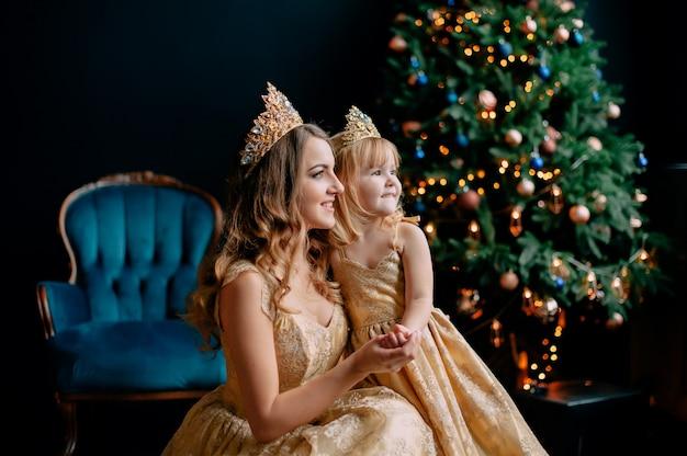 Mutter und tochter in luxuriösen kleidern in der nähe von weihnachtsbaum, studio