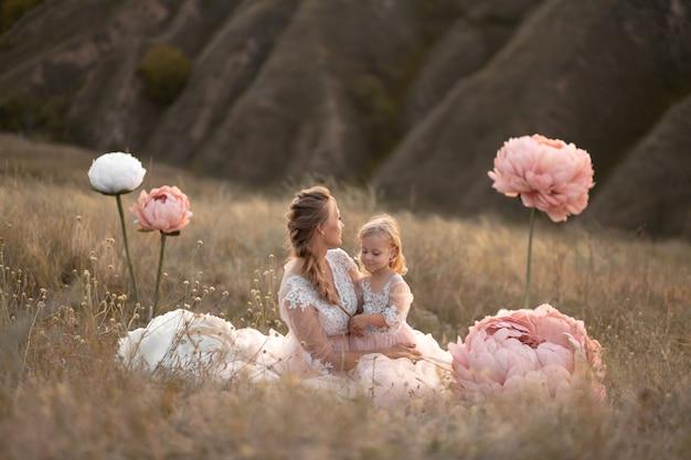 Mutter und tochter in rosa märchenkleidern sitzen auf einem feld, umgeben von großen rosa zierblumen