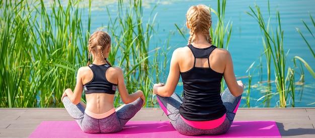 Mutter und tochter in sportbekleidung sitzen auf der matte am pier in der nähe des wassers im freien