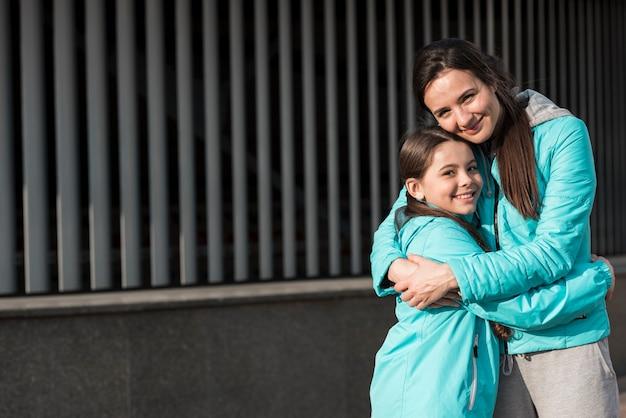 Mutter und tochter in sportswear umarmen mit kopierraum