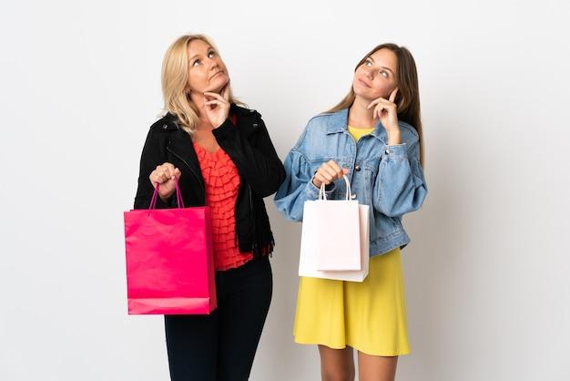 Mutter und tochter kaufen einige kleider isoliert auf weißer wand, die eine idee denken, während sie kopf kratzen