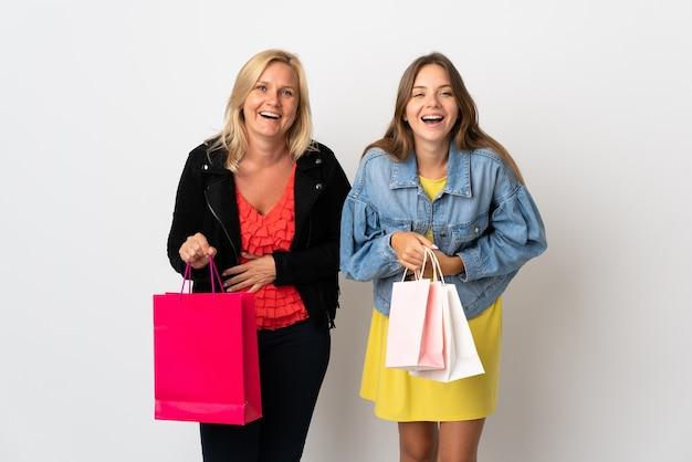 Mutter und tochter kaufen einige kleider isoliert auf weißer wand, die viel lächeln, während sie hände auf brust legen