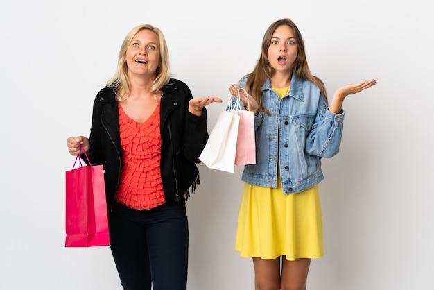 Mutter und tochter kaufen einige kleider isoliert auf weißer wand mit überraschung und schockiertem gesichtsausdruck