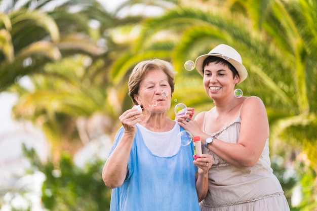 Mutter und tochter kaukasisches paar spielen zusammen seifenblasen in der freizeit im freien. defokussierter natürlicher grüner hintergrund. portraits von fröhlichen und verspielten menschen zusammen in freundschaft