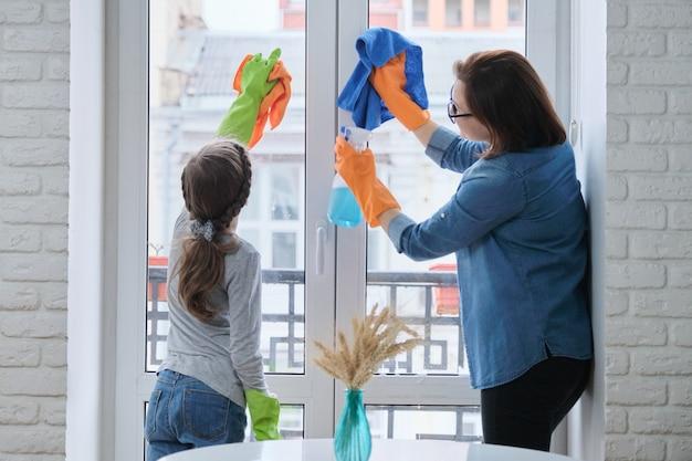 Mutter und tochter kind in gummihandschuhen mit waschmittel und lappen waschfenster zusammen. mädchen, das frau hilft, hausreinigung zu tun