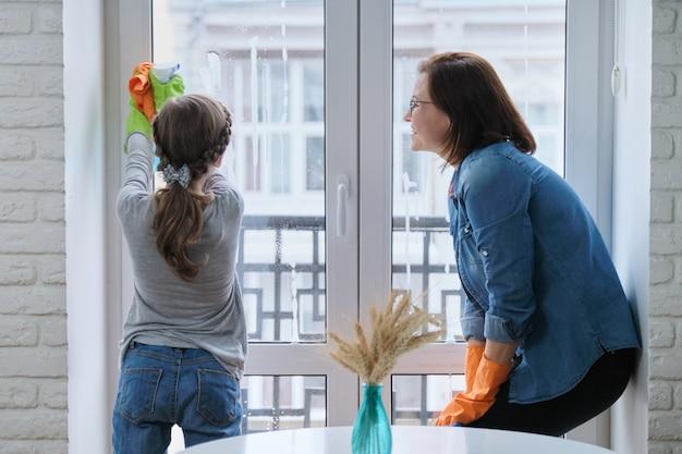 Mutter und tochter kind in gummihandschuhen mit waschmittel und lappen waschfenster zusammen