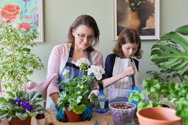 Mutter und tochter kind pflanzen topfpflanzen, blumen. hobbys und freizeit, pflege, familie, zimmerpflanze, konzept für zu hause eingetopfte freunde