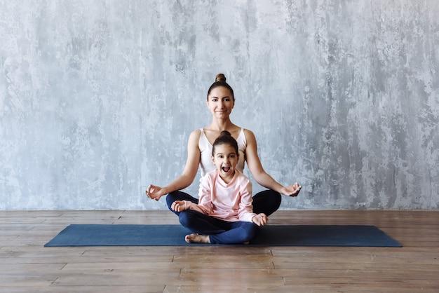 Mutter und tochter-kind praktizieren yoga, während sie zusammen im lotussitz sitzen