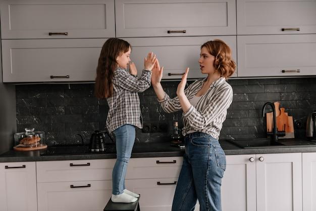 Mutter und tochter klatschen in die hände und posieren in der küche.