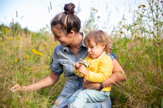 Mutter und tochter kleinkind sammeln einen strauß wildblumen blumen schafgarbe nahaufnahme