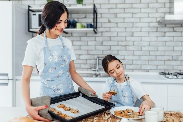 Mutter und tochter kochen gemeinsam kekse in moderner weißer küche