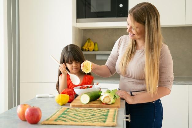 Mutter und tochter kochen gemüse zum abendessen am küchentisch. mädchen und ihre mutter dressing salat in schüssel mit der hälfte der zitrone. familienkochen oder gesundes ernährungskonzept