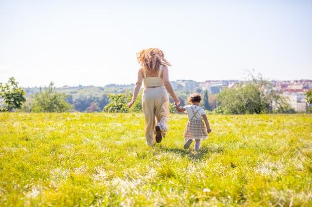 Mutter und tochter lachen und haben spaß im park das konzept einer glücklichen familienfreundschaft und liebe