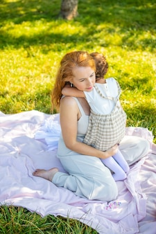 Mutter und tochter lachen und umarmen sich auf einer decke im park sitzend das konzept einer glücklichen familie...