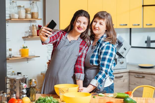 Mutter und tochter lächeln und posieren in der küche