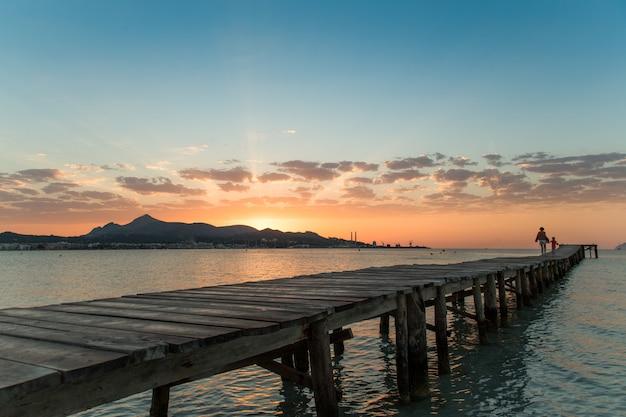 Mutter und tochter laufen entlang des piers in richtung des wunderschönen und wunderschönen sonnenaufgangs auf mallorca