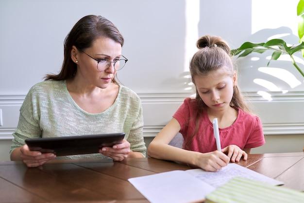 Mutter und tochter lernen zusammen zu hause und sitzen am tisch. frau mit digitaler tablette, internet verwendend, mädchenschreiben im notizbuch. fernunterricht, eltern helfen kind grundschüler
