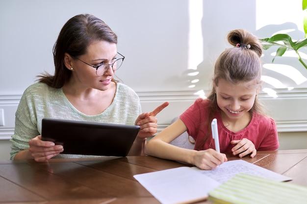Mutter und tochter lernen zusammen zu hause und sitzen am tisch. frau mit digitaler tablette, internet verwendend, mädchenschreiben in notizbuch. fernunterricht, eltern helfen kind grundschüler